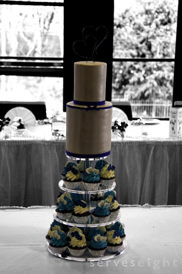 A tall skinny two tier cake atop a tower of cupcakes with fondant hearts stamped with the couple's initials.