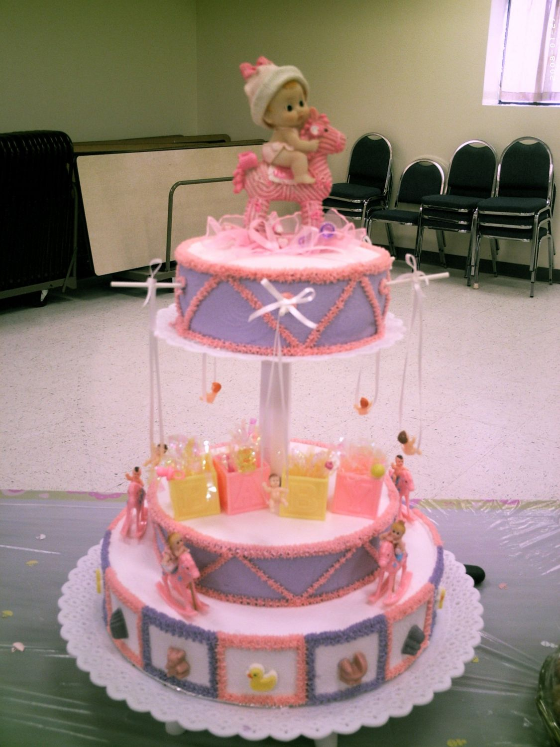 3 tier baby shower cake. Top layer has babies swinging, middle layer is setting on top of the bottom layer. Bottom layer has rocking horses with babies rocking and decorated with baby candy molds set around on each block square. I made this cake for my niece.