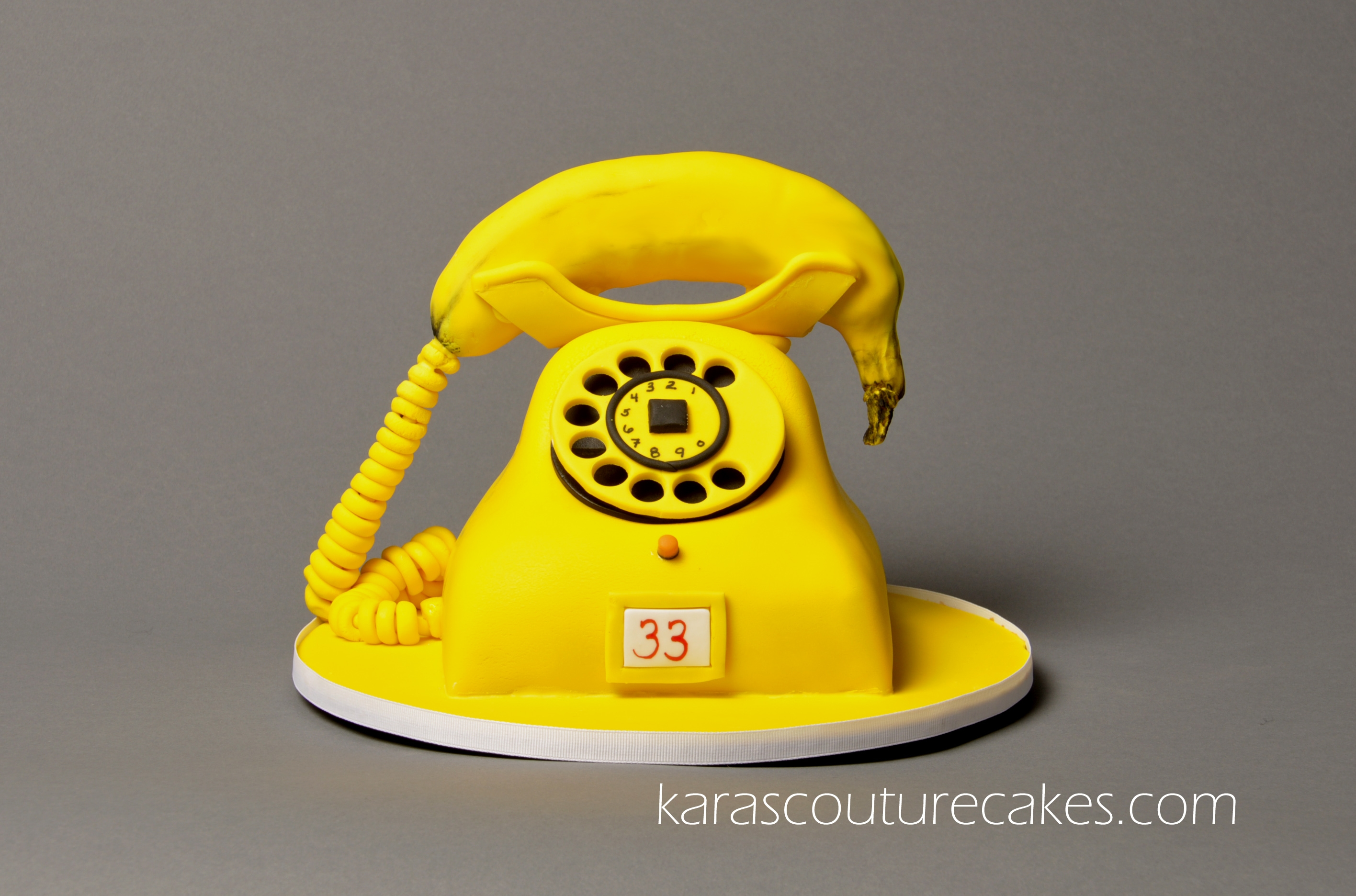 A sculpted banana phone cake requested for a 33rd birthday.