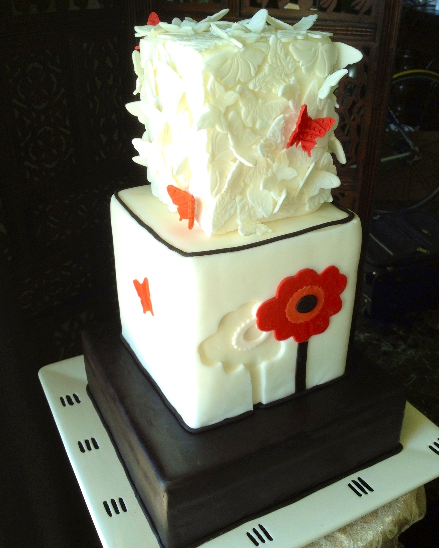 Cake by: The Vagabond Baker-Custom Cakes and Sweets with a Global Influence. Square 3 tier with butterflies covering top tier and a single red poppy shadowed by a cut-out of same poppy. I made this display cake for a silent auction to raise money for GCA an organization that I am involved with that builds schools and orphanages in Haiti.