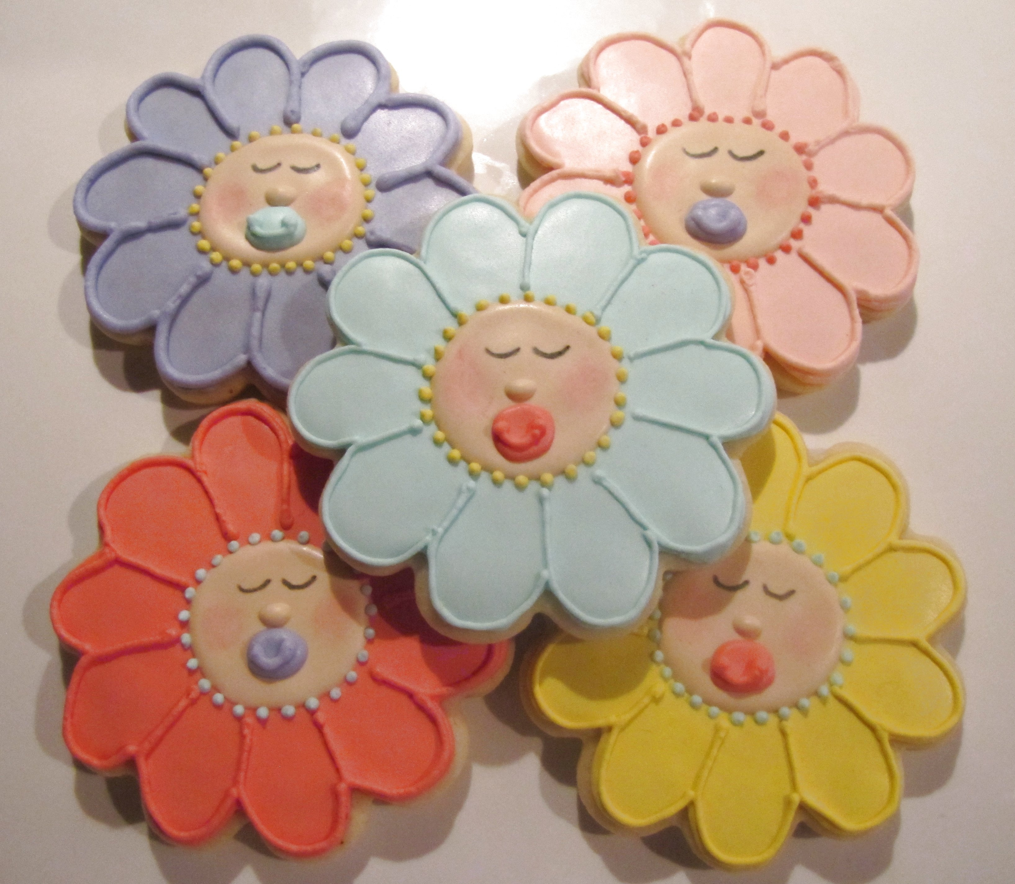 Baby flower faces for a baby shower.  Vanilla sugar cookies with a modified RI.  Pink petal dust on cheeks.  Design inspired by Sugarbelle.  Sorry for the poor quality photo; had to take it at night.  Colors were more pastel.