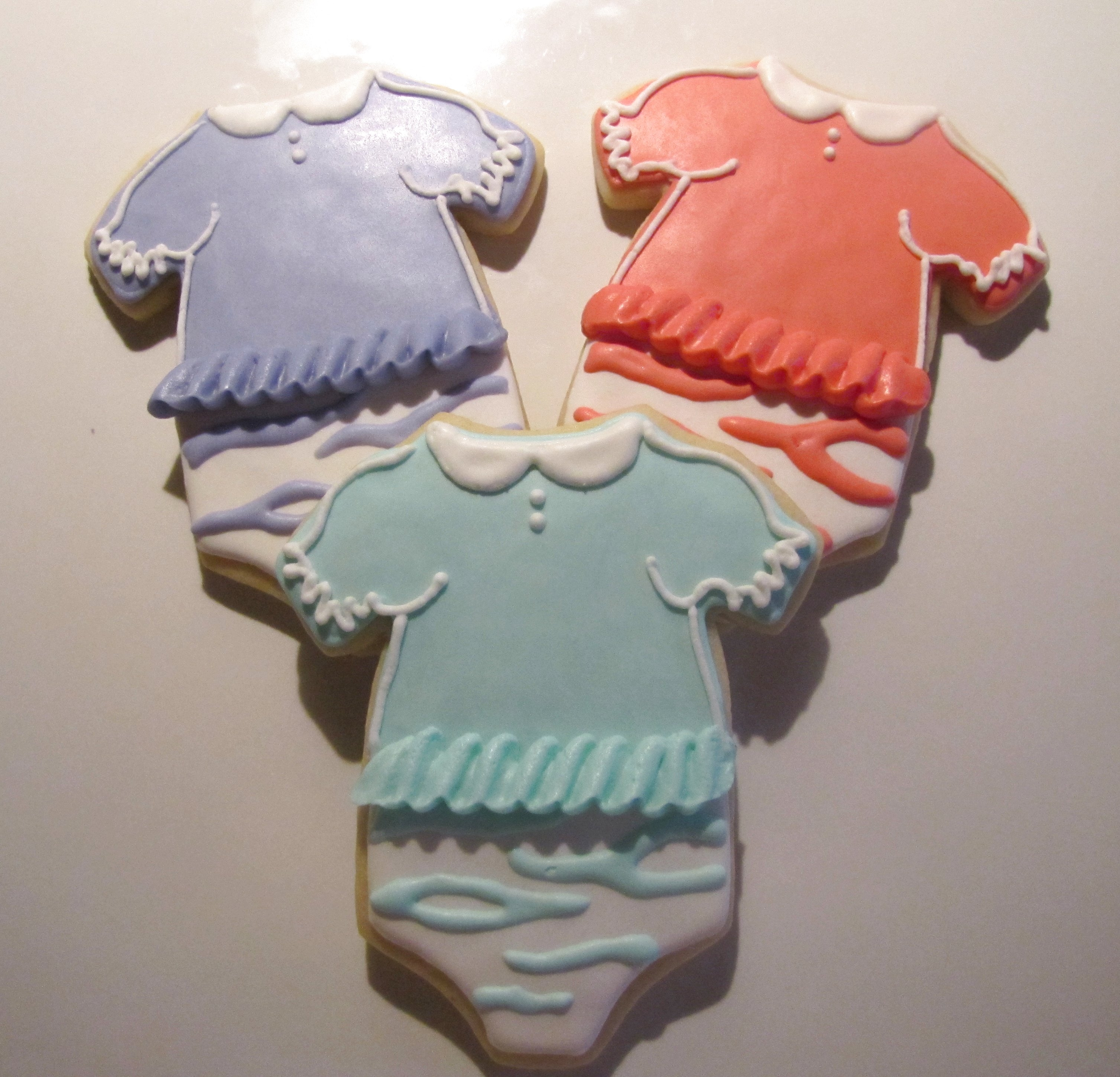Baby girl onesies with ruffles & zebra stripes.  Vanilla sugar cookies with a modified RI.  Sorry for the poor quality photo; had to take it at night!  Colors were more pastel