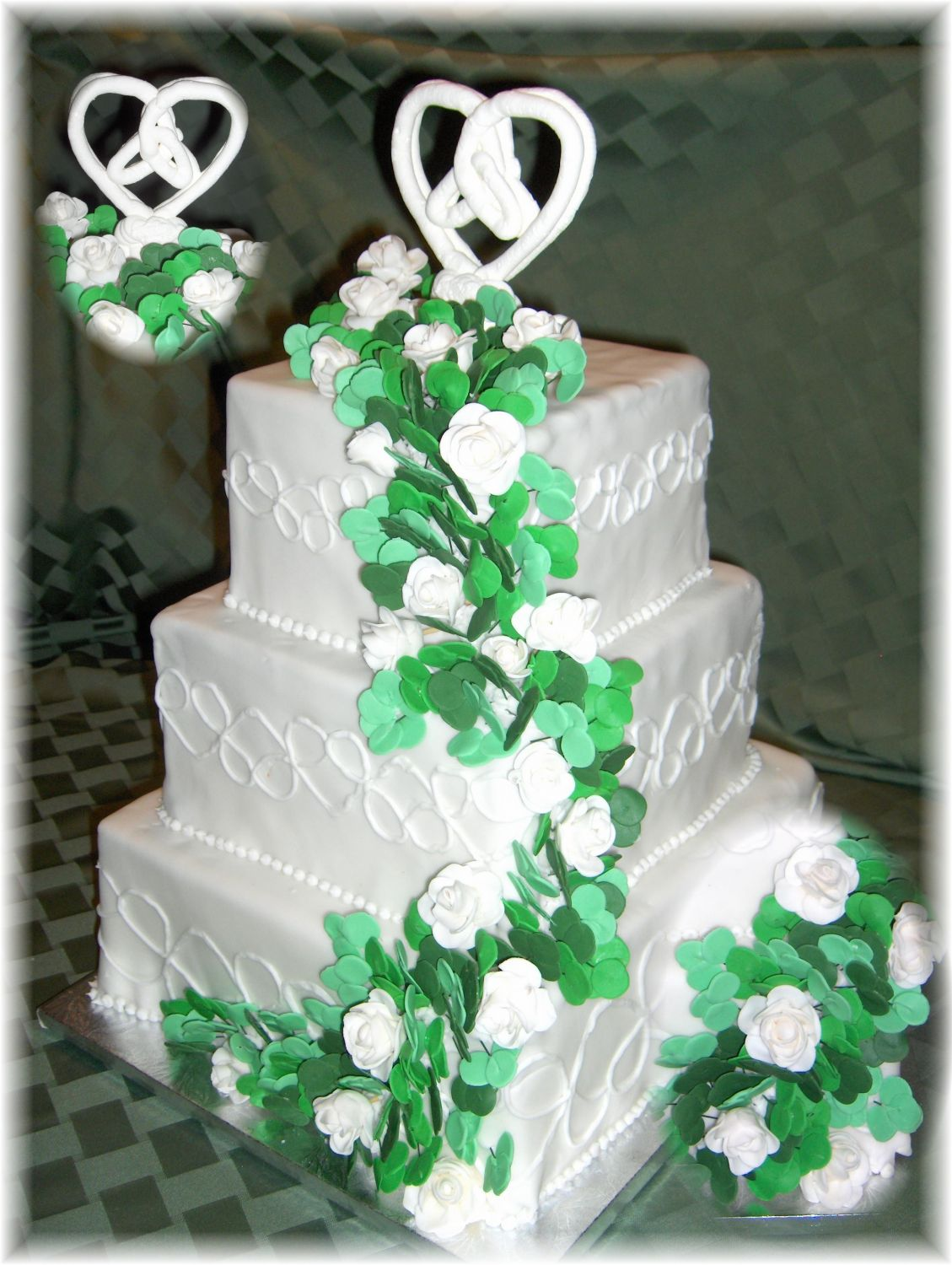 This cake ws designed around the Irish Trinity Knot.  It is a fondant covered cake with a royal icing cake topper in the shape of the Trinity Knot.  There are close to 100 gum paste shamrocks and 20 white gum paste roses on this cake.  The sides are decorated with Trinity Knot as well.  This picture includes a close up of the topper as well as the shamrocks.
