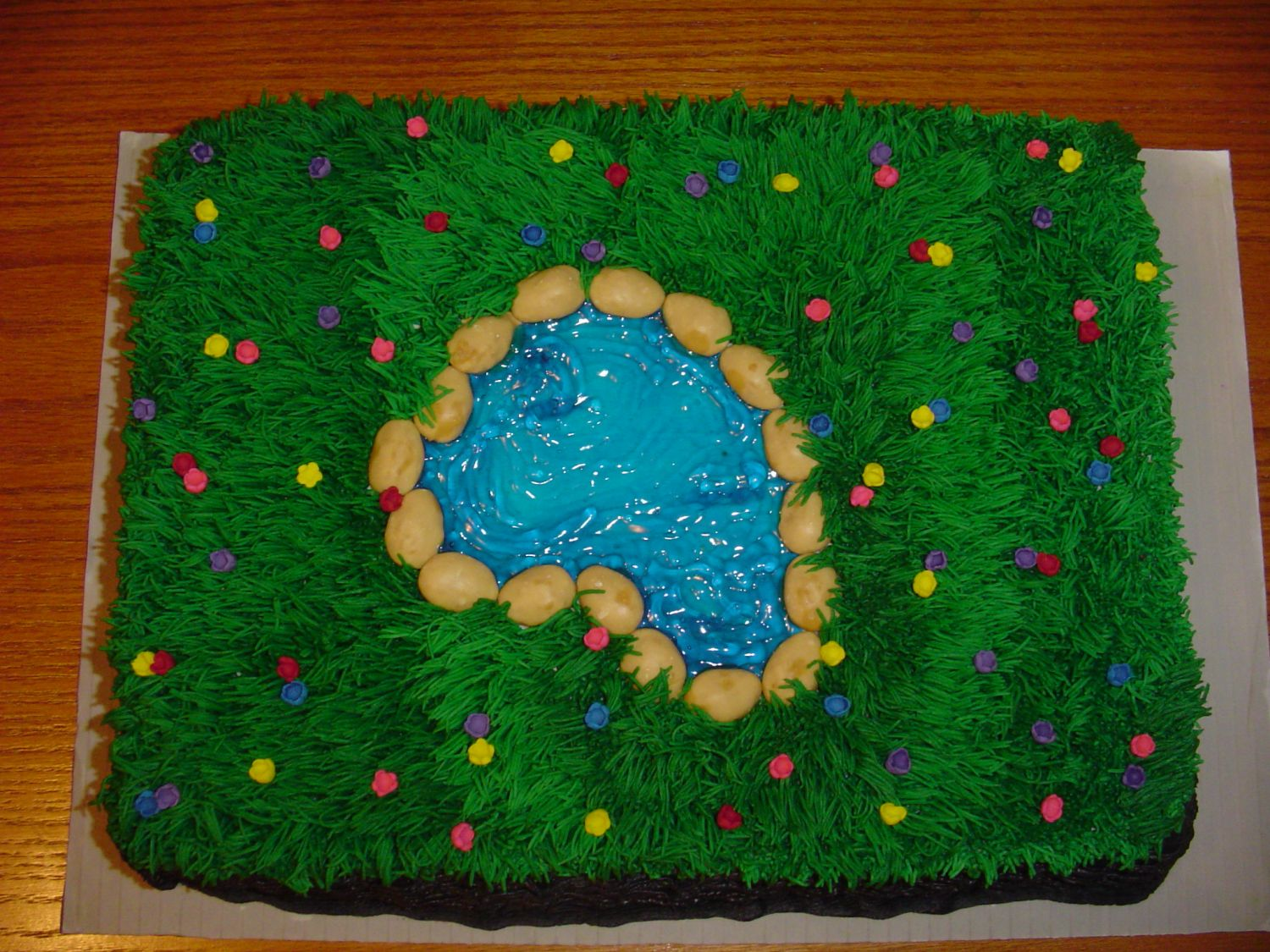 Cake is a Yellow cake. Baked in two 9 inch pans. Grass made with Wilton tip. Rocks around pond are Maple Nut Goodies (candy). The pond was made with Blue Gel Icing. Flowers made out of Gum Past.