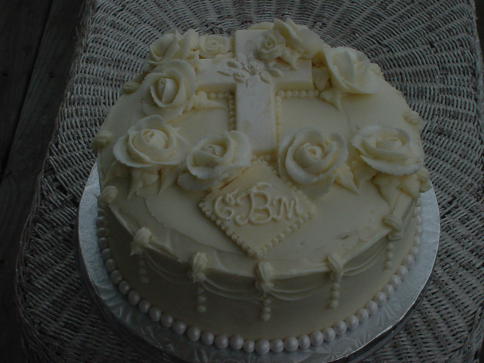 "Vanilla cake, homemade raspberry filling, buttercream covered.  Fondant pearls at the base with ""chocolate"" cross and monogram."