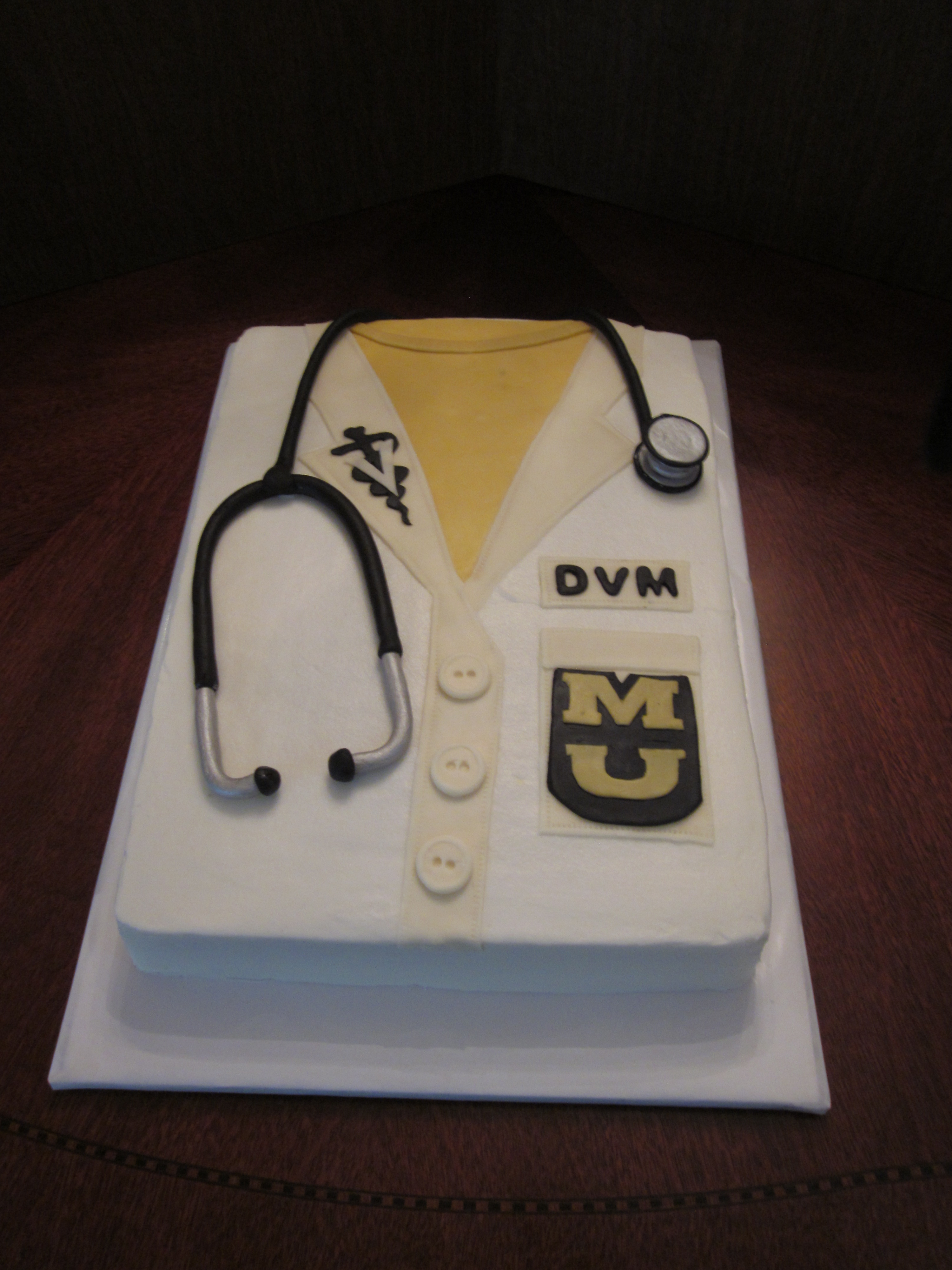 Made this cake for a friend who was receiving his white coat in Veterinary school. BC with fondant accents