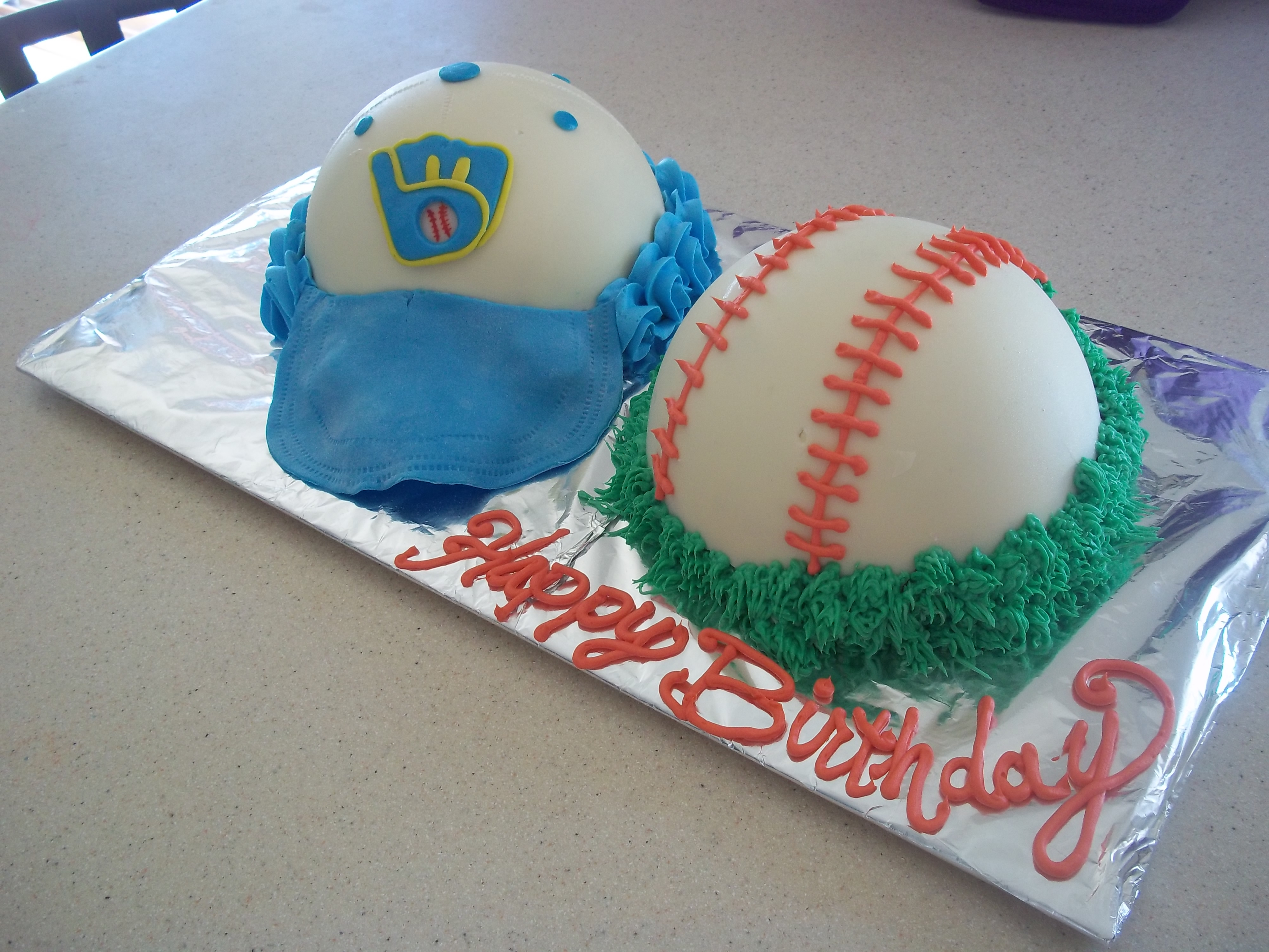 Milwaukee Brewers red velvet 6' sphere cake. The cake is filled with cream cheese frosting covered in white chocolate, with fondant logo and rim of hat, grass and lines of the baseball are piped.