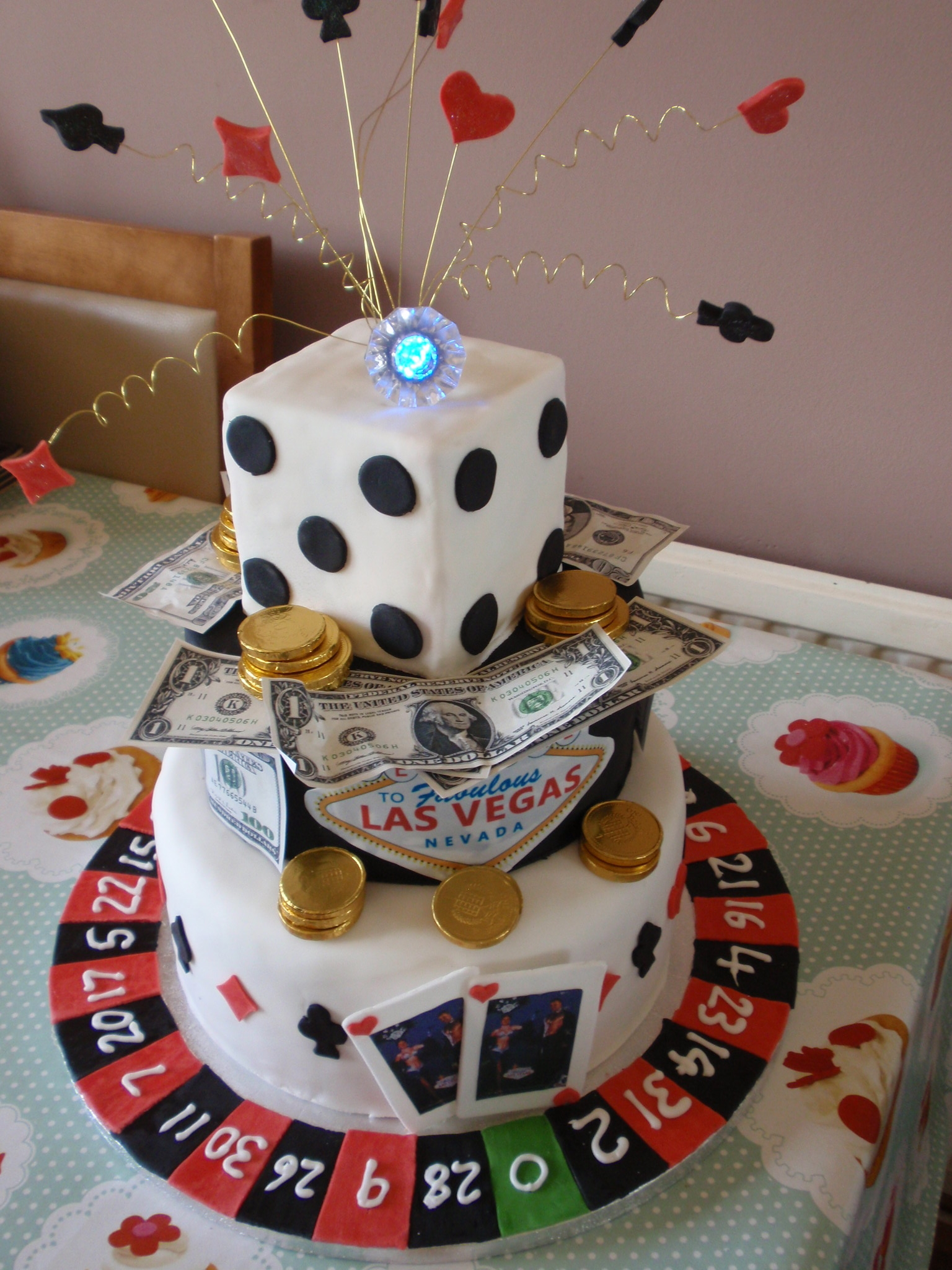 Basic sponge cake base, chocolate middle tier and cake dummy dice. Flashing ring on top and fondant accents. Made for my daughters engagement party