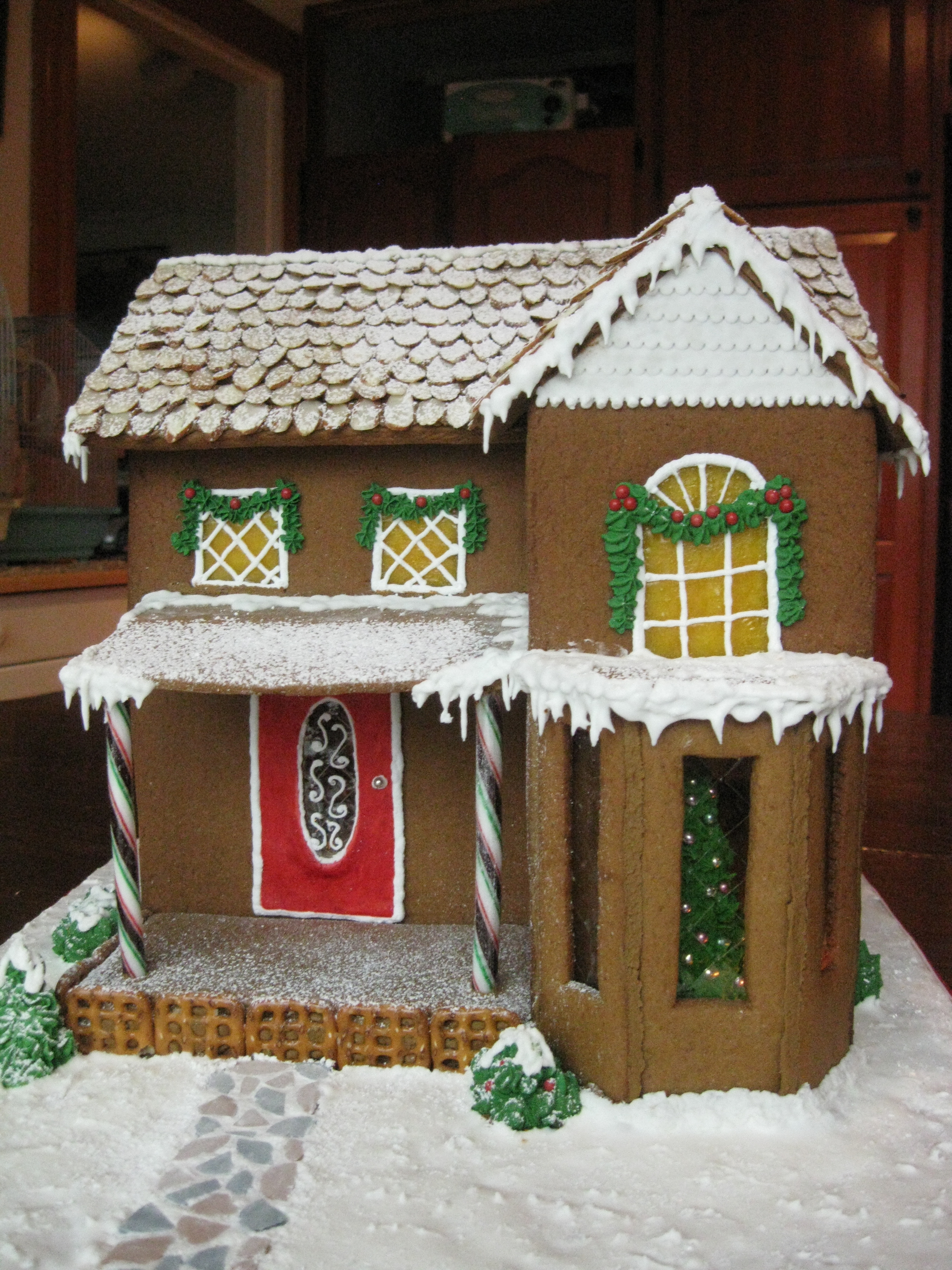 All materials are edible. Gingerbread, Gumpaste, Royal Icing, Almonds, Necco wafers, candy, pretzels. Tree in window is Royal Icing with dragees; Bay window panes are leaf gelatin. Thanks for looking!