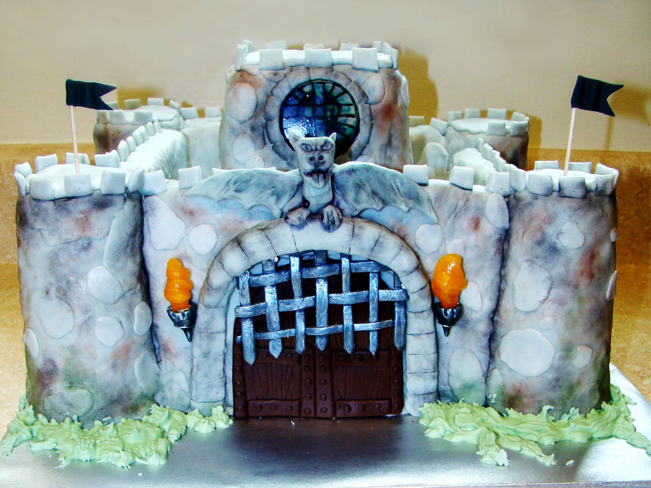 Castle cake insides were vanilla bean cake with vanilla bean buttercream. The outside walls and towers are fruity pebble rice crispy treats (request of the customer) and those were covered in frosting and fondant. The door is made out of modeling chocolate. The gate is made out of black gumpaste and painted with metallic paint to give it a shiny iron look. The gate accidentally got stuck on there crooked, but it kept falling otherwise. The gargoyal is made out of modeling chocolate. The torches are made out of gumpaste and the fire is made out of pulled sugar. The stained glass windows are made out of melted sugar that were poured into molds and food colors were painted on the back to give it that look of being stained glass. It took a lot of trial and error, but finally have a decent method for those. 