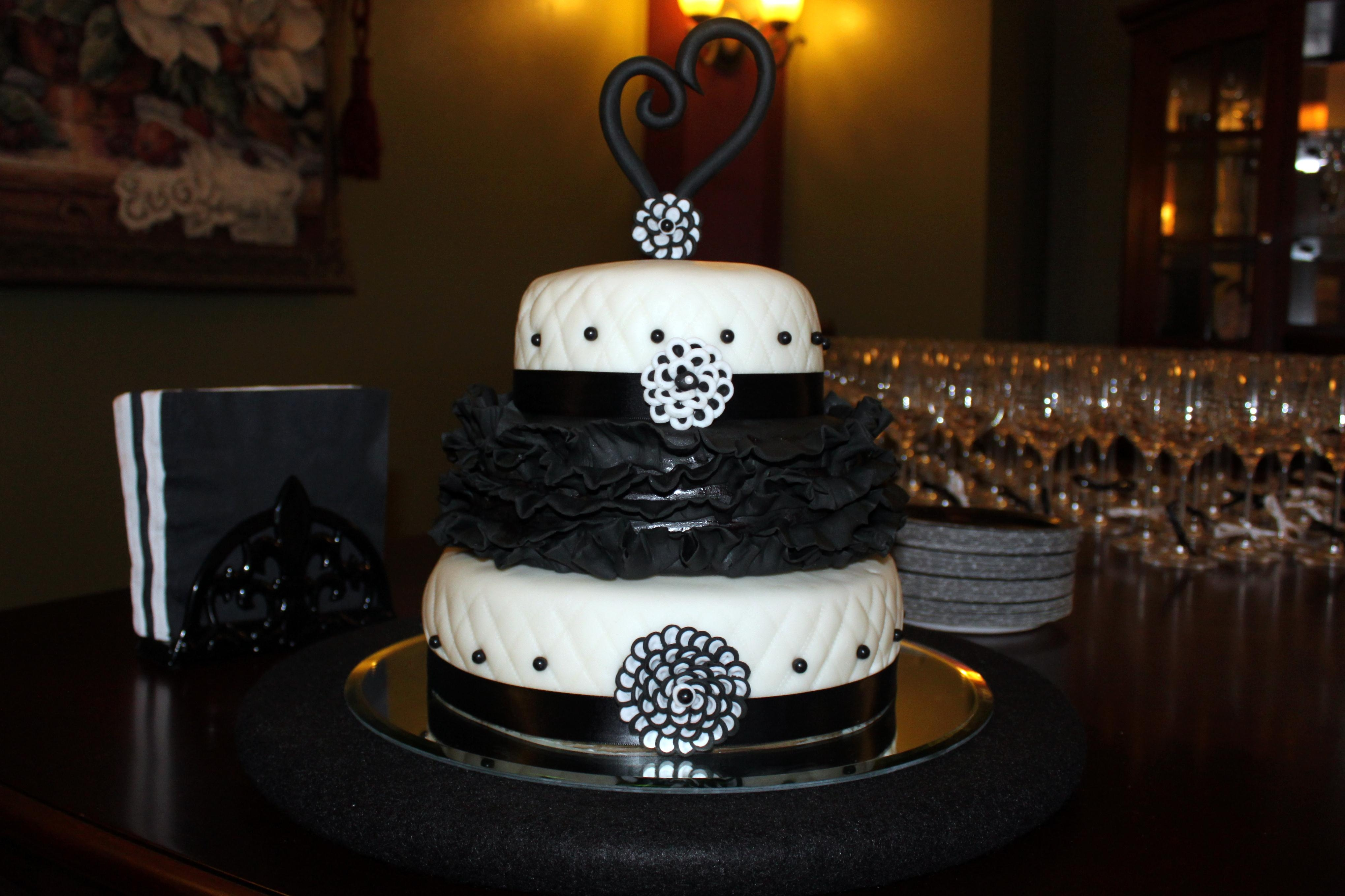Black and White Engagement Cake for a black and white themed engagement party.  Cake is champagne flavored filled with raspberry mousse, covered in white chocolate ganache and fondant