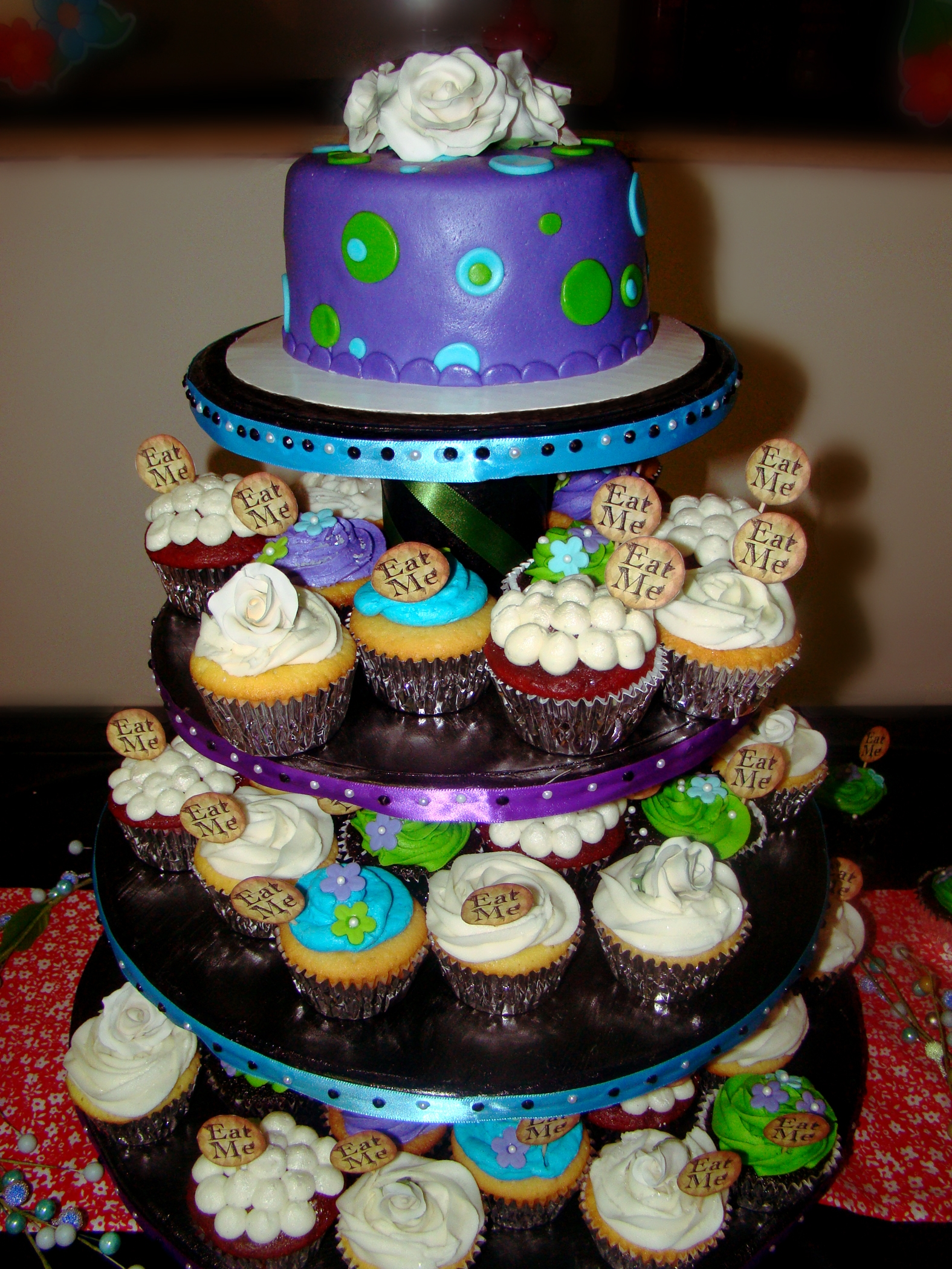 A cupcake tree and 6 inch cutting cake done in the theme: Alice and Wonderland Tea Party, through the looking glass. 