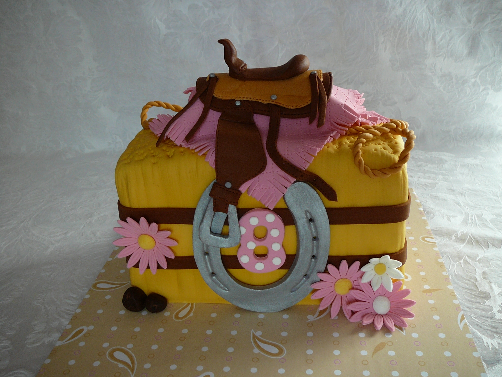 A western saddle on a bale of hay for a 8 years old girl. I put sliver luster dust on the horseshoe to make it look like real. This is a red velvet cake with creamcheese filling all covered with fondant. All details are fondant.