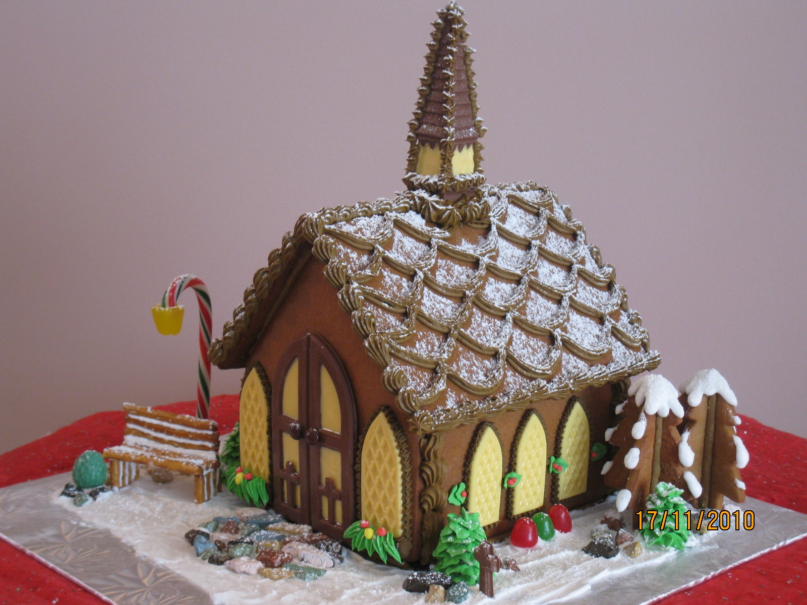 Chocolate steeple, windows and door, and angel on back wall.  Wreath is gingerbread cookie iced with royal icing. All decorations are edible.