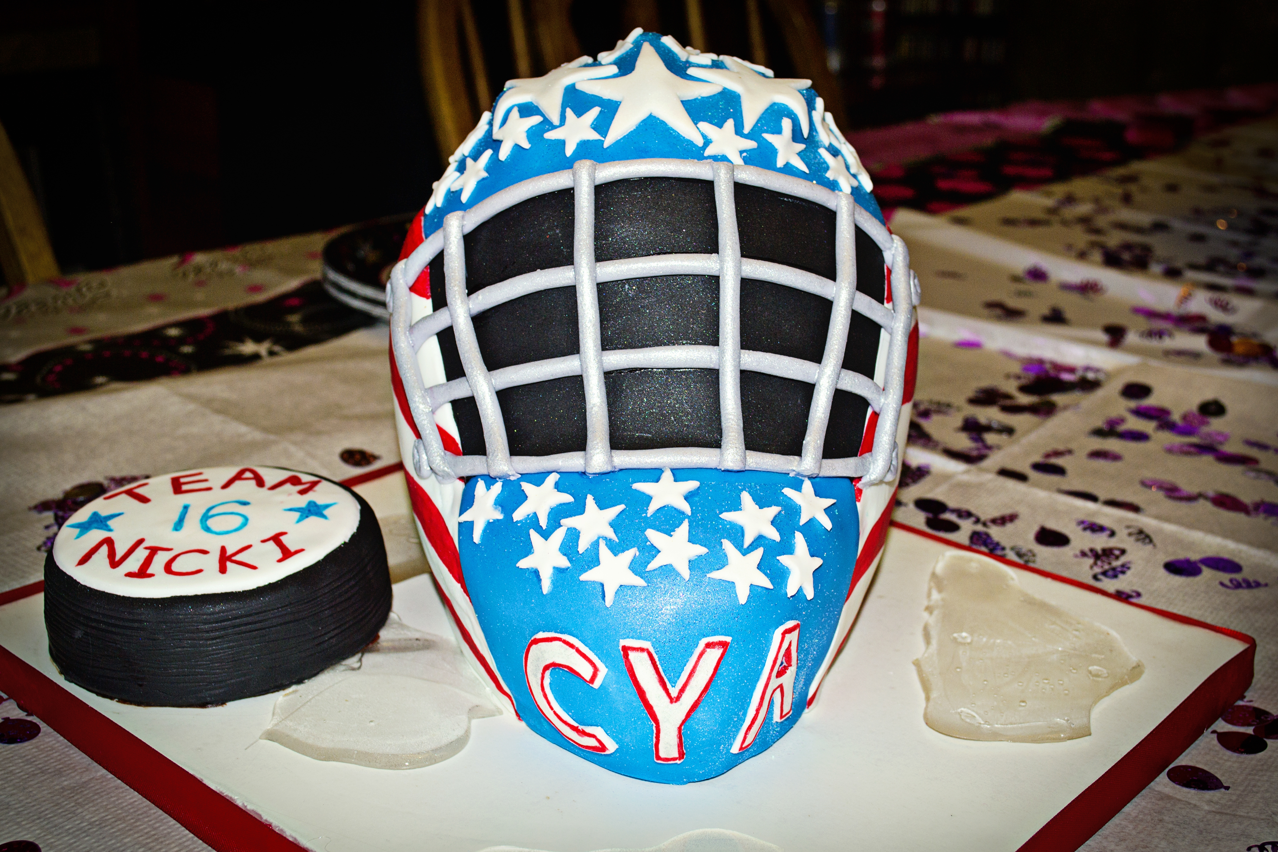 "3D hockey goalie mask carved out of a wondermold pan and 9x13 cake cut in half and stacked. Thanks to puppylove for the help with the mask.  Puck is cake. ""ice"" is made from isomalt."