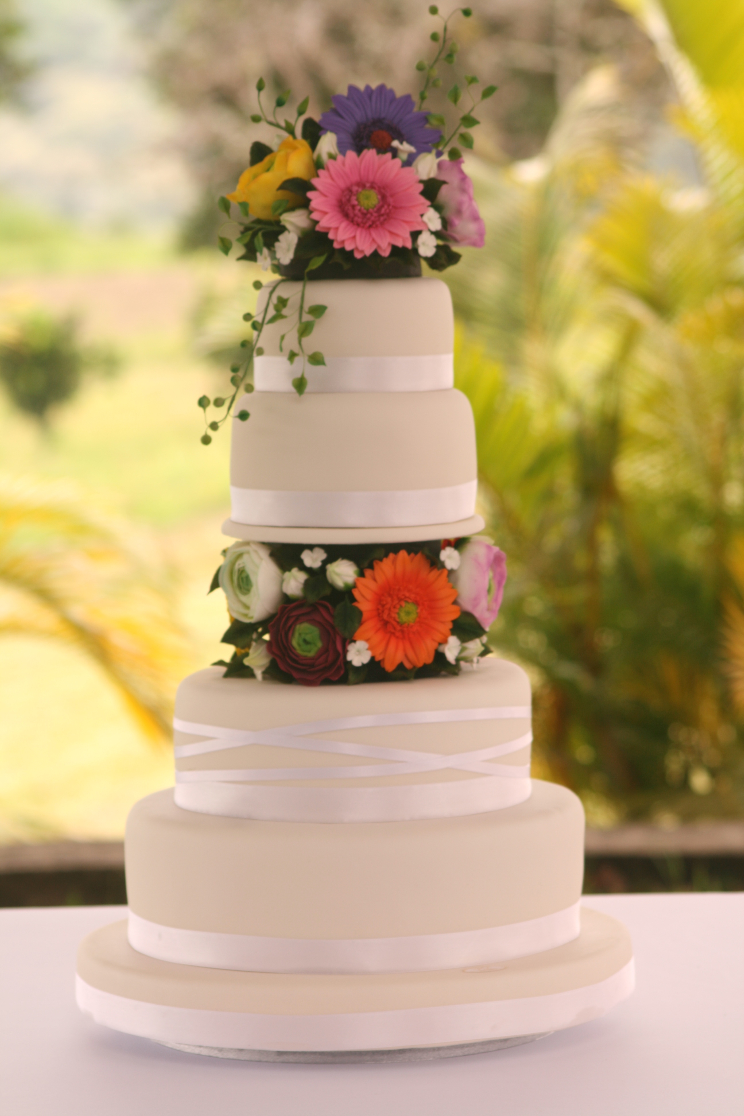 Four tiers wedding Cake, with gerberas and Ranunculus flower, all handmade and edibles