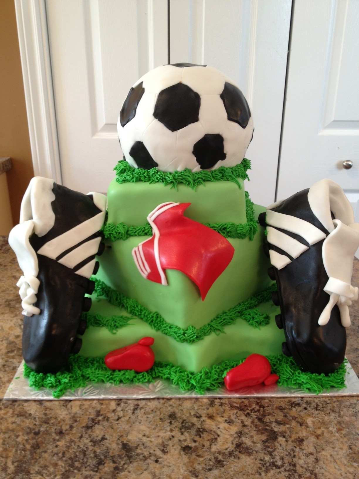 A cake I made for a gala supporting one of our local soccer teams going to Nationals. This was the centerpiece of their auction gala and went for over $1000! Cake is vanilla covered in buttercream fondant and accents are fondant an dbttercream. Cleats are RCT covered in BC and Fondnat