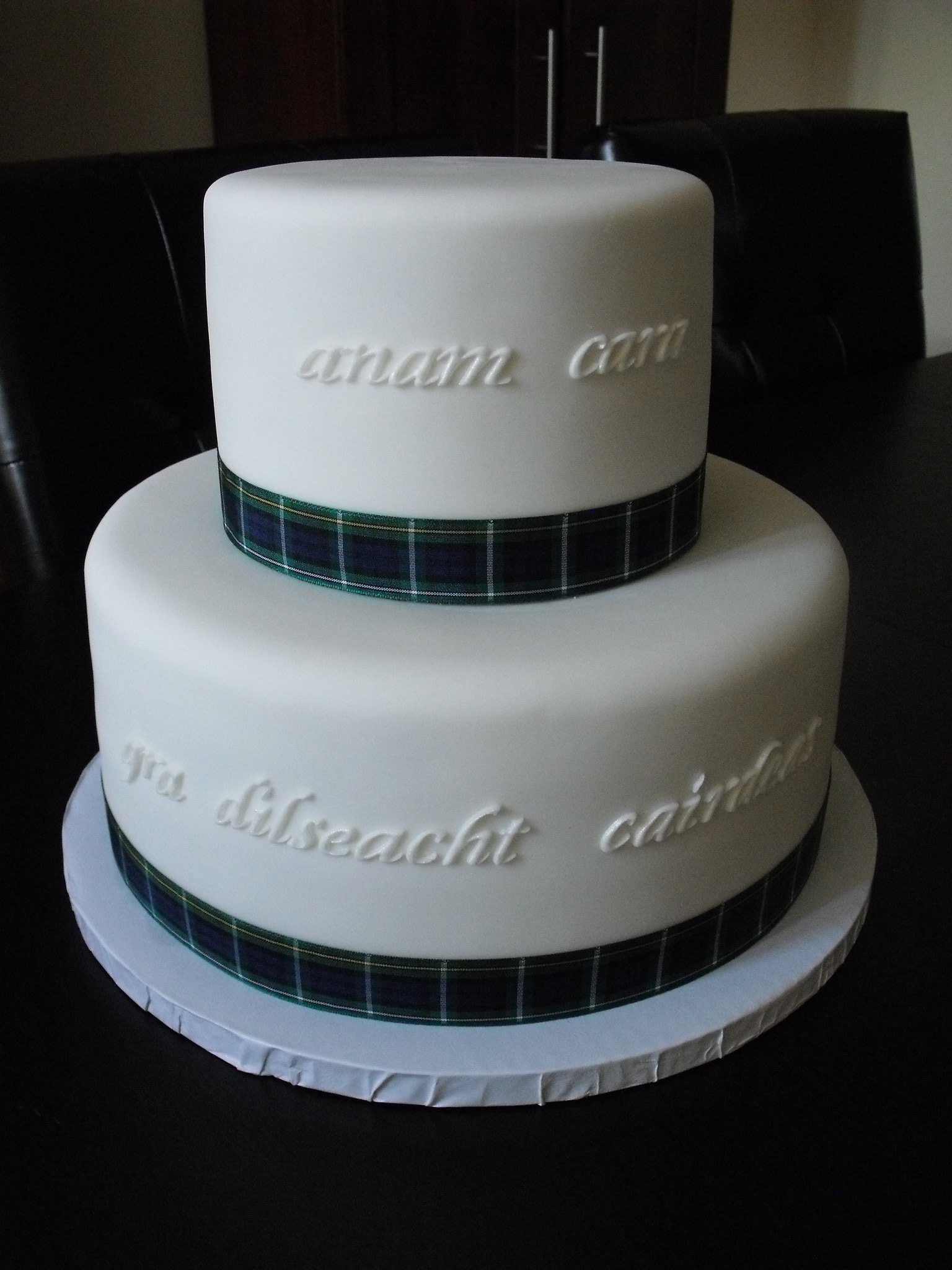"Wedding cake for a couple having a scottish themed wedding. Script on cake reads ""Soul mate"" and ""love loyalty friendship"". Ribbon was imported from scotland and provided by bride."