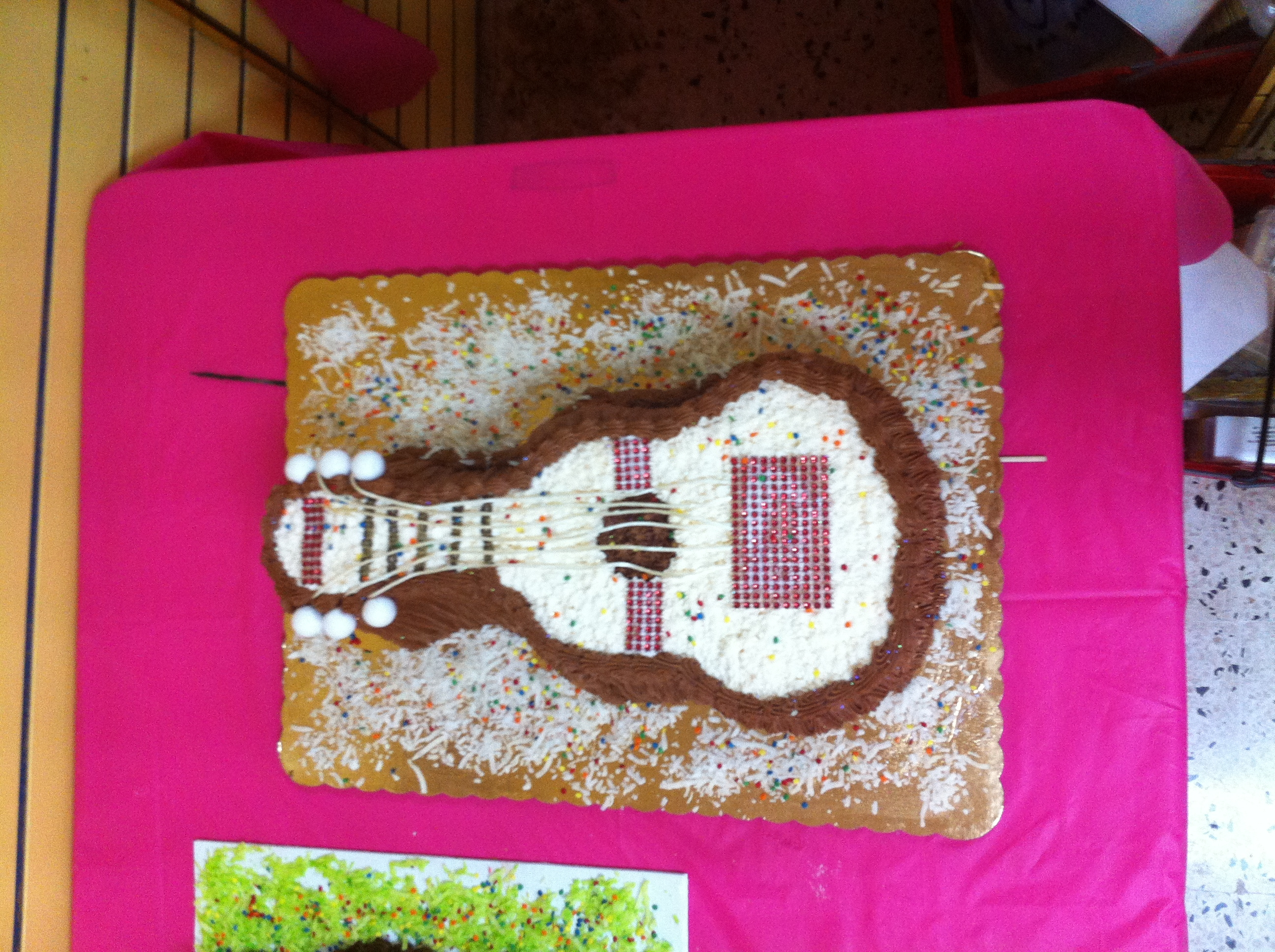 "This is a cake I did for my pastry design class. It is a 5"" silhouette of a music guitar. I decorated it with string and foam balls at the tips to make it look more realistic. It is a simple butter cake with royal icing."