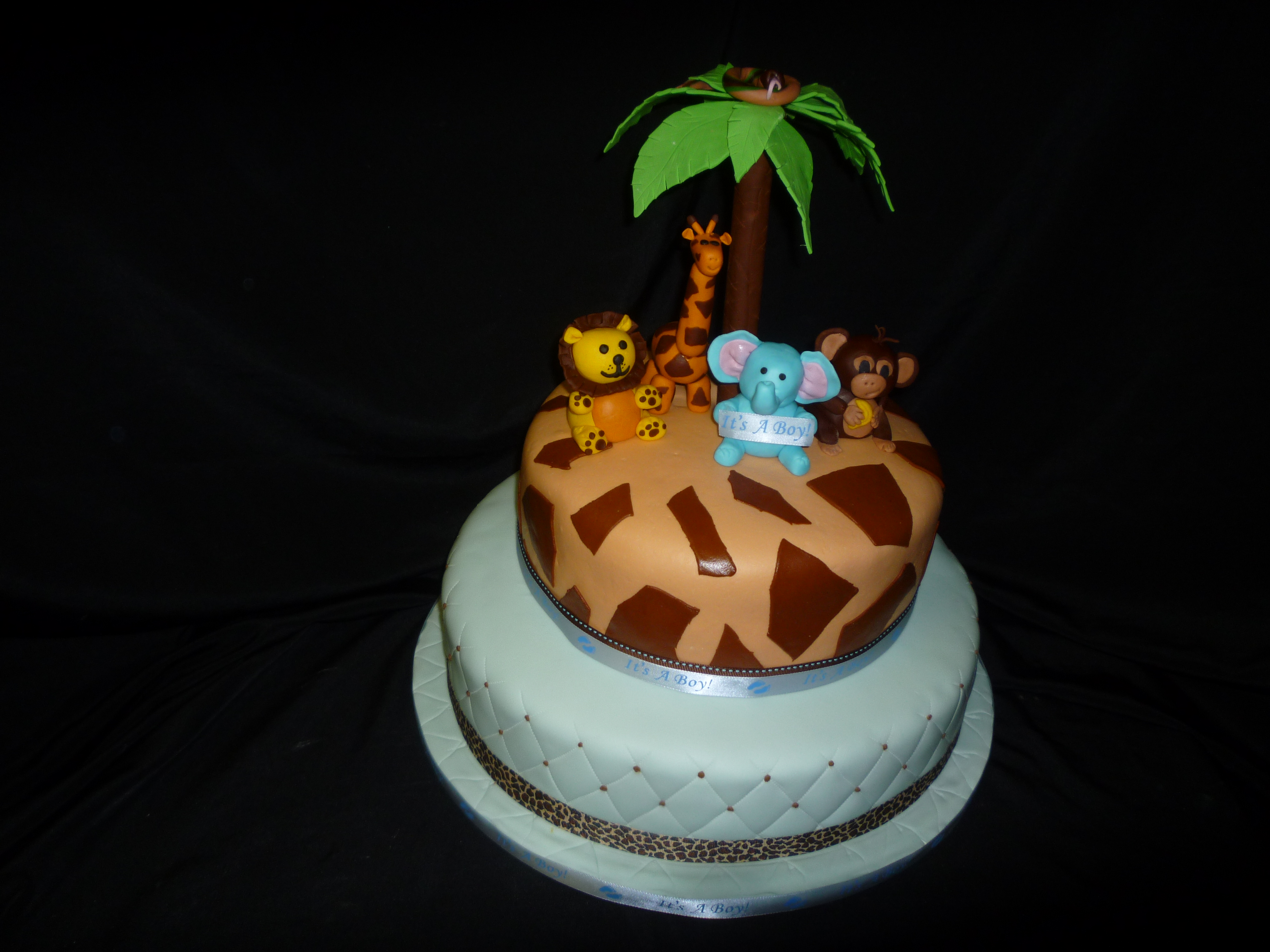 "All animals and palm tree are hand made from gumpaste/fondant. Top tier is 10"". Bottom tier is 14"", quilted with chocolate buttercream dots."
