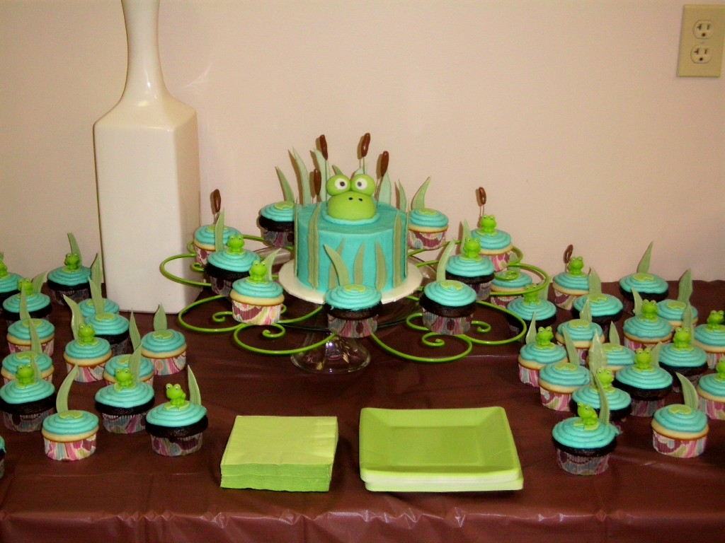 Baby shower cake & cupcakes. Cake is chocolate with buttercream frosting topped with fondant frog. Cupcakes are white & chocolate with buttercream frosting. Small frogs are plastic toppers. Lily pads are gumpaste. Cattails are fondant