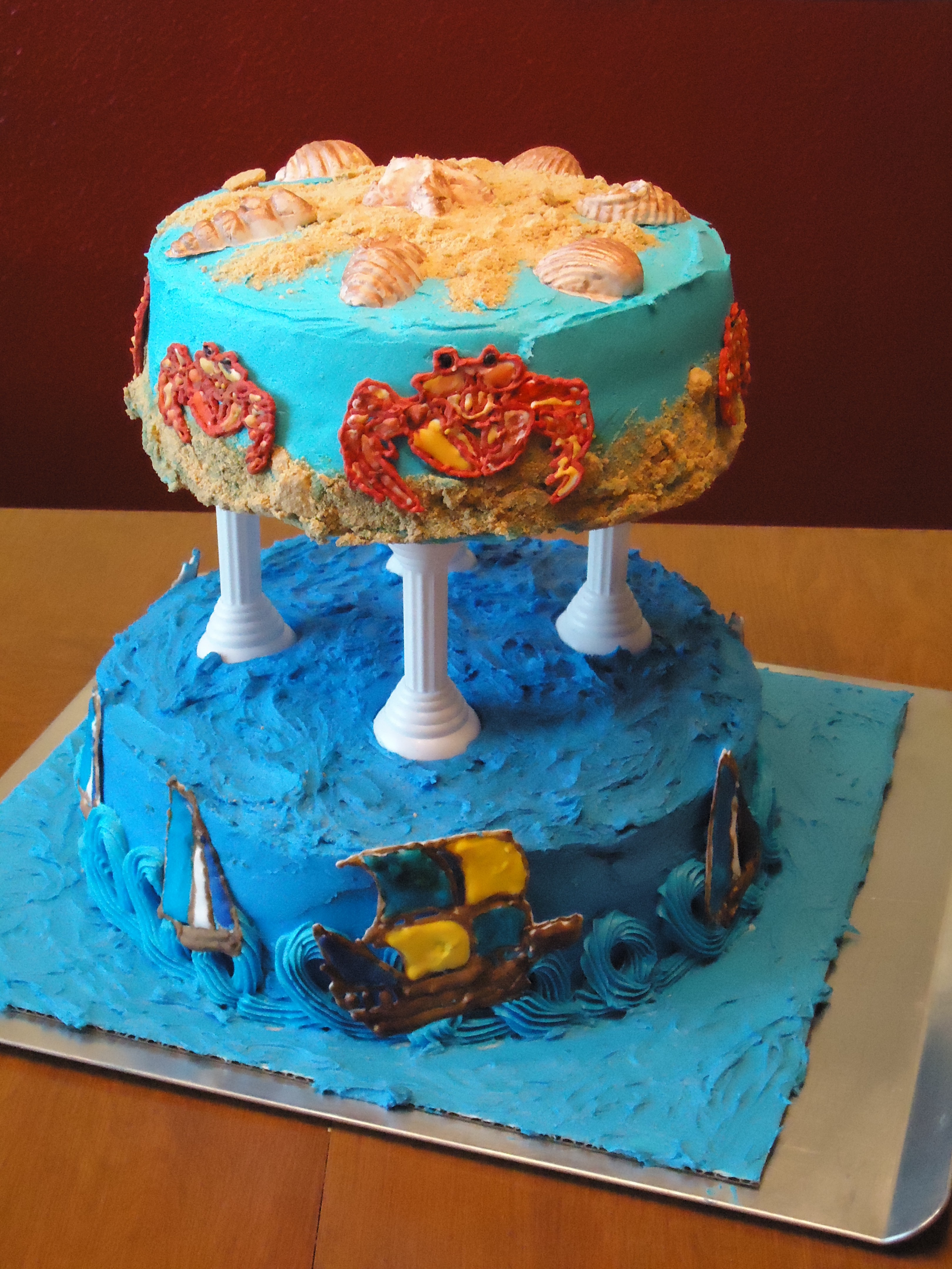 Two tier cake with sailing ships and crabs made from color flow and sea shells made from gum paste. The sailing ships and sea shells were hand painted, the sea shells using pearl dust mixed with water