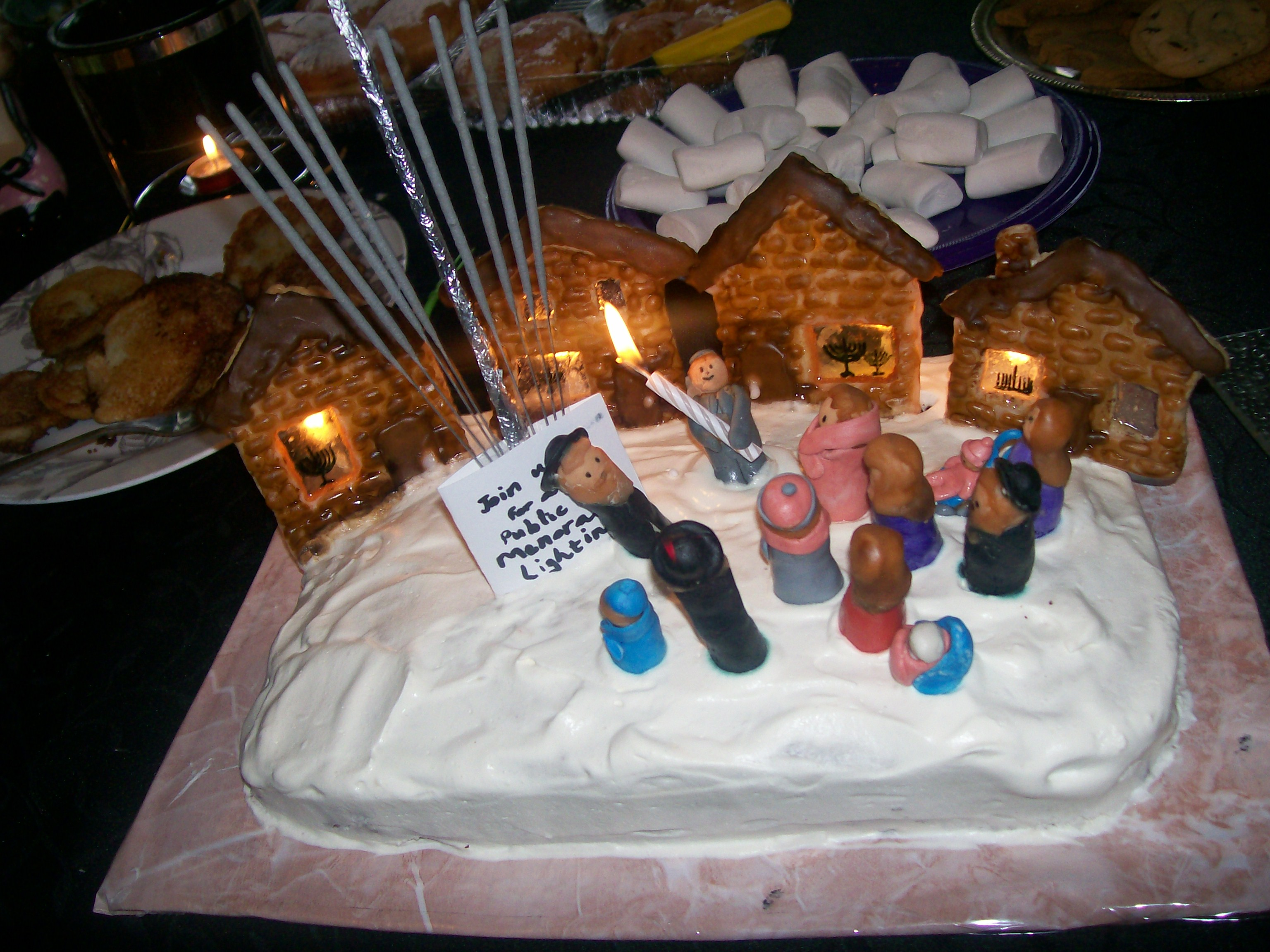 This cake depicts the scene of a Public Menorah Lighting on Chanukah. All of the Jewish people in the village are gathered around the giant menorah (made of sparklers) in the town square. 