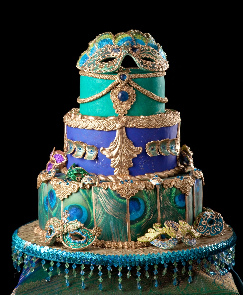 Cake madewith edible images in the peacock theme and colors. Masks are made of gumpaste and then piped and painted.