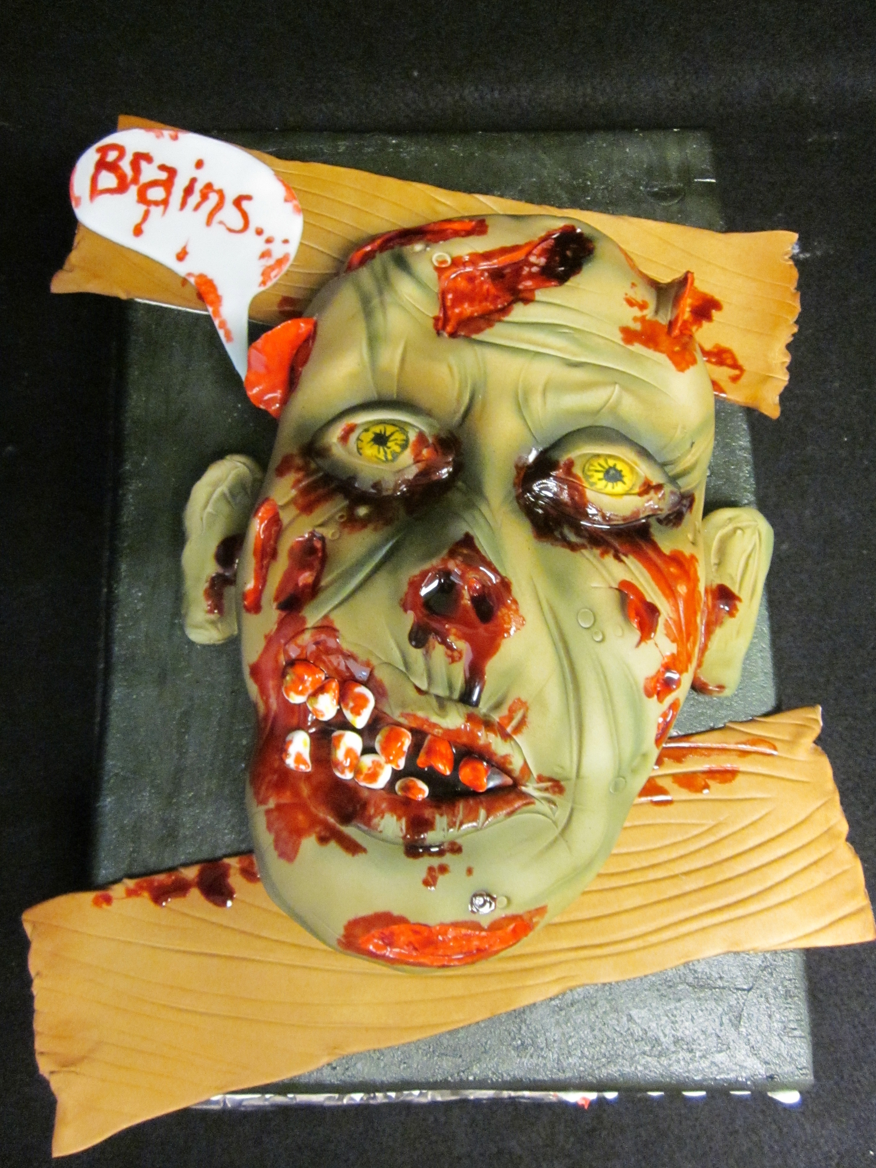 Zombie face coming out of a sheet cake, lookin for some brains! Face moulded with RKT and fondant....strawberry flavored edible blood! Yum!