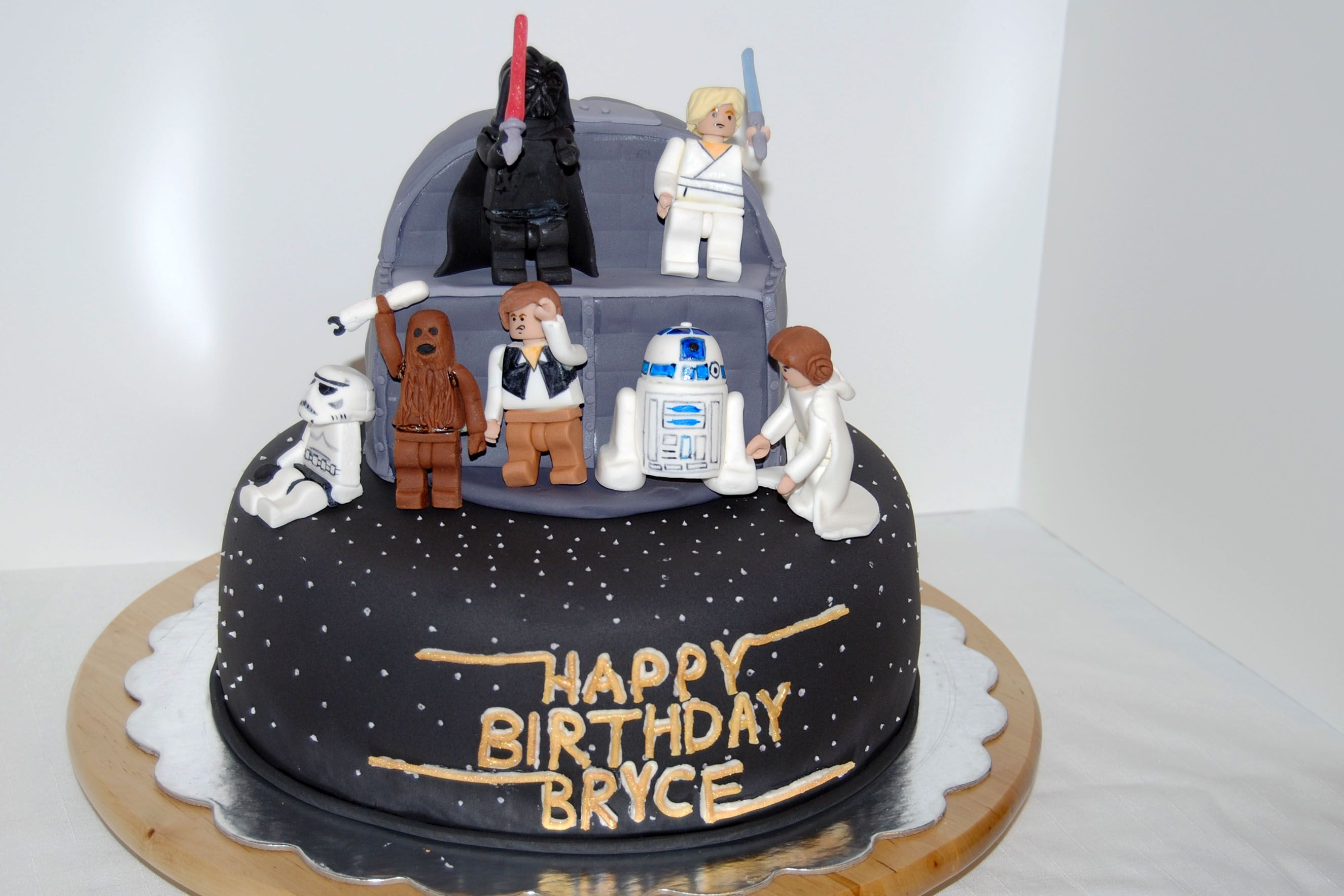 "My son LOVES Lego Star Wars and thanks to the Lego Batman Cake youtube video he figured this would be a no-brainer for Mom! All fondant, the characters are standing on the ""death star"" . The lettering is also fondant dusted with gold luster dust and attached with buttercream. Luke is leaning a little because I didn't attach them to the cake until we got to the venue."
